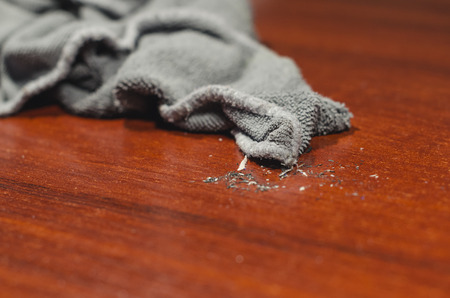 Grey wet rag on the dirty wooden desk. Cleaning the house or doing household chores concept.