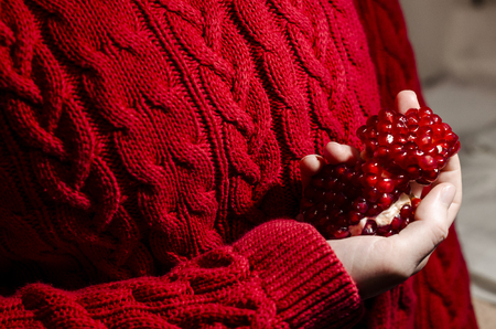 Peeled pomegranate in the hands of a human. Red sweather is on the background. Fresh organic food close up. Stay healthy concept.