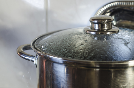 Cooking metal pan with lid covered with condensate water drops is on the stove. Kitchen background close up. Boiling water concept.
