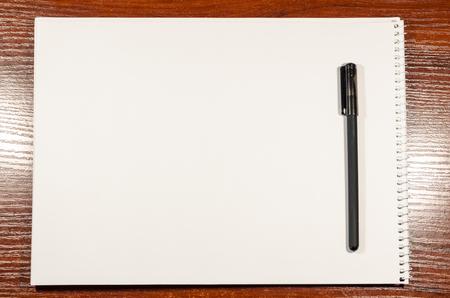 Auf dem Holztisch liegt eine leere Seite eines offenen Notizbuchs mit einem schwarzen Stift. Platz zum Schreiben von allem, was Sie wollen. Geschäfts- und Bildungskonzept. Texturhintergrund eines weißen Blattes Papier.