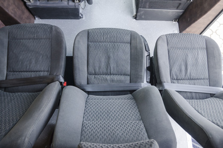 Wide top view on interiors of the back of the car. Mild grey passenger seats of the bus. Transport saloon concept.