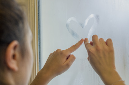 Woman hands drawing a heart on the sweaty foggy window. Water droplets condensation background of dew on glass, symbol of love close up. Be happy and love even in bad raining weather outside concept. 免版税图像