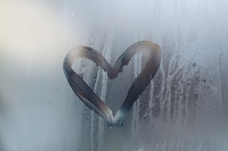 A heart is drawn on the sweaty foggy window. Water droplets condensation background of dew on glass, symbol of love close up view. Be happy and love even in bad raining weather outside concept.