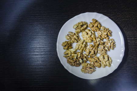 Pieces of walnuts on the white plate on the dark wooden kitchen table. The process of making food concept. Organic healthy fresh food close up view. Stockfoto
