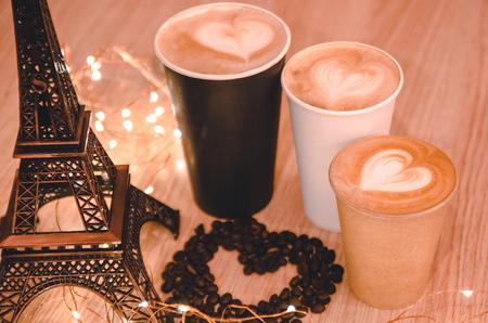 Een hart gemaakt van koffiewinsten op de houten tafelachtergrond tussen speelgoed uit de Eiffeltoren en afhaalkoffiebekers. Een cadeau voor je paar op Valentijnsdag concept. Latte art met een symbool van liefde.