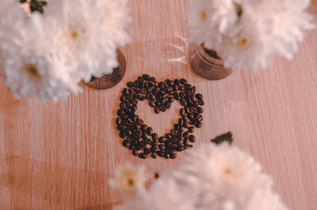 A heart made out of coffee grains on the wooden table background between three bouquets of white flowers. A gift, present for your couple. Happy Valentines day concept. The symbol of love out of food.