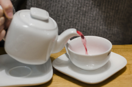 Pouring fruit red tea from the teapot into white cup concept. Eating breakfast on the wooden table background. Dinking a hot drink in the coffee shop.