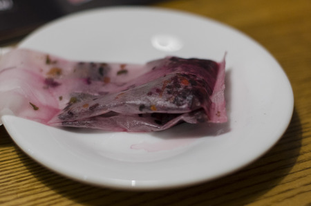 Tea bag of fruit red tea on the white plate close up view. Making and drinking hot tea concept.