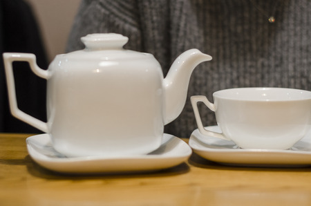 White tea set of a cup and teapot concept. Eating breakfast on the wooden table background. Dinking a hot drink in the coffee shop.