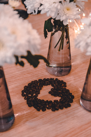 A heart made out of coffee grains on the wooden table background between transparent vases with water. A gift, present for your couple. Happy Valentines day concept. The symbol of love out of food. Reklamní fotografie