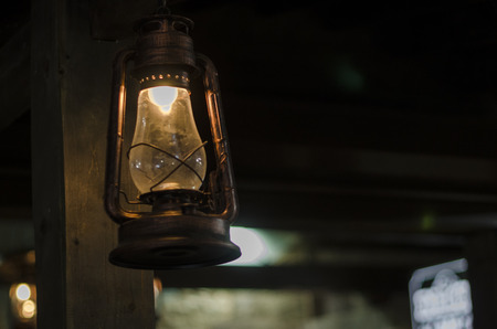 Old lamp hanging from the ceiling on the dark background. Burning kerosene lamp close up view. Room lighting concept.