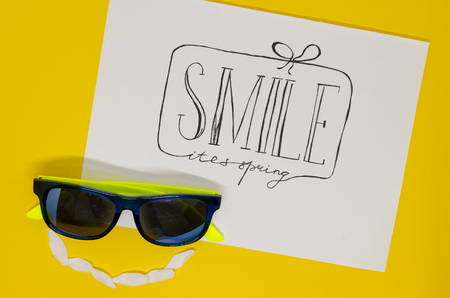 White notebook where is written with nice handwriting: Smile its spring, isolated on yellow background. Hello spring greeting concept. A gift as a frame with a smiling face made out of sunglasses Reklamní fotografie