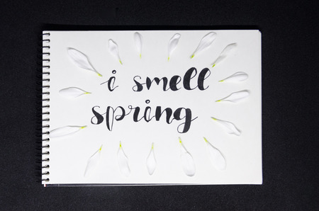 White page of a notebook where is written with nice handwriting: I smell spring, isolated on the black  background. Hello spring concept. White leaves of a flower