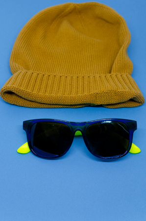 Yellow hat isolated on a blue background. A face made out of a hat and sunglasses concept. Reklamní fotografie