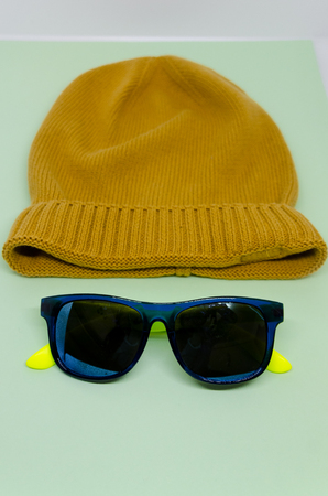 Yellow hat isolated on a light blue background. A face made out of a hat and sunglasses concept.