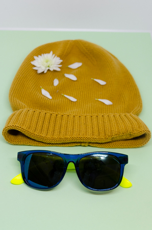 Yellow hat with white flower and petals and isolated on a light background. Clothes and nature concept. A face made out of a hat and sunglasses.