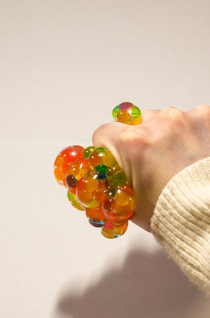 Colored antistress in the human hand isolated on the white background. Squeezing a toy with your palm. Stay relaxed concept.