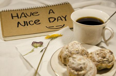 Desayuno en la cama con café, galletas y flores. Que tengas un buen día concepto. Comience su mañana con una sonrisa en su rostro.