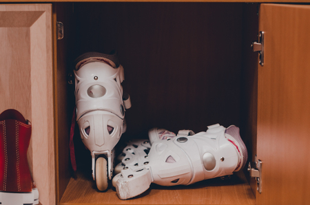 A pair of white roller skates in the wooden shelf close up view. Skating and havng fun concept. Keeping sport equipment in the locker. Imagens