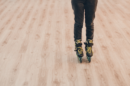 A human wearing black old roller skates on the roller rink from the front view. Green laces close up view. Ready to skate concept.
