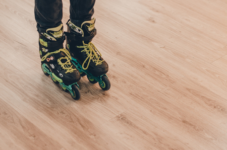 A human wearing black old roller skates on the roller rink from the front view. Green laces close up view. Ready to skate concept. Stok Fotoğraf - 123251037