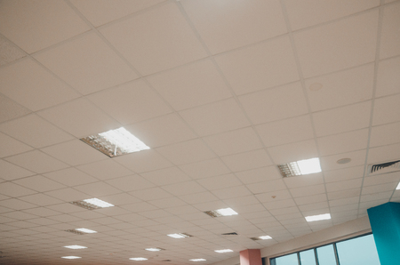White ceiling with shining lamps. Room inside interiors concept. Lighting up the building.