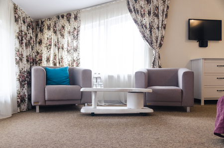 Interiors of the room in the hotel concept. A sofa with a blue pillow and a white table with water bottles.