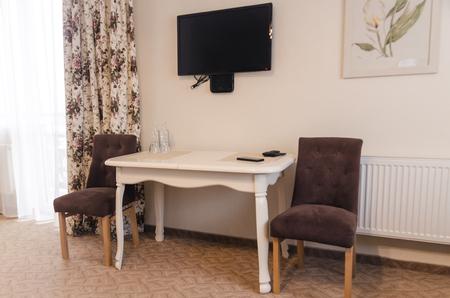 Concepto de interiores de habitaciones de hotel. Dos sillones, un televisor negro y una mesa vista de cerca. Muebles de dormitorio en la casa. Foto de archivo
