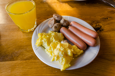 A white plate with food and a silver fork are on the wooden table. Ready to eat concept. Tasty food close up. Grilled kebab, sausages and mashed potatoes with orange juice.