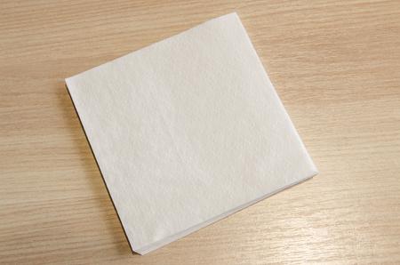 Un tovagliolo bianco su uno sfondo di tavolo in legno. Rimani pulito mentre mangi il concetto.