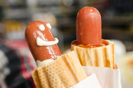 Two baked hot dogs in the human hand. Junk food concept. Freshly made sausages in dough with melted cheese. Eat tasty. A smiling face made with mayonnaise. Фото со стока