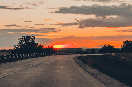 orange sunset view with shining sun and clouds from the car front window. Driving car during sunset concept. Background of nature landscape and a road. 版權商用圖片