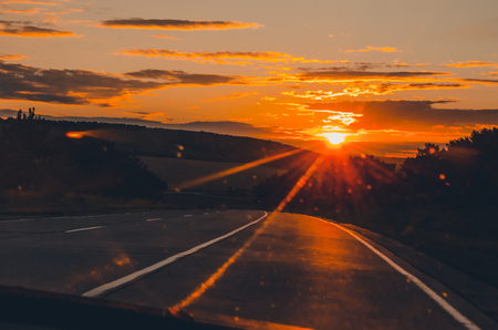 orange sunset view with shining sun from the car front window. Driving car during sunset concept. Background of nature landscape and a road.