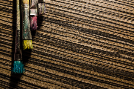 A collection of paint brushes on the wooden background with copy space. Art equipment for drawing.