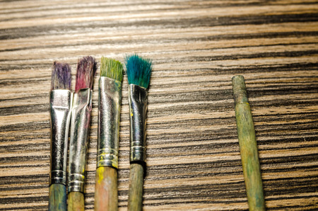 A collection of paint brushes and one broken brush apart on the wooden background. Art equipment for drawing. Stock fotó