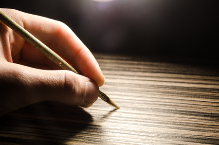 paint brush in the human hand on the wooden background with a shining light behind. Art equipment for drawing with copy space.