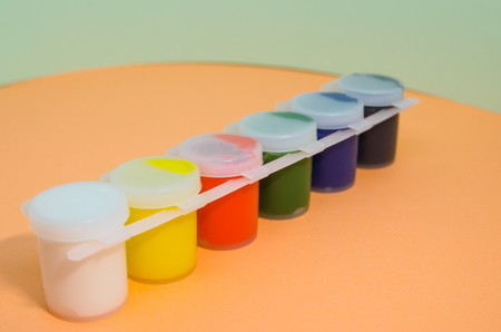Multicolored gouache on an orange background. A set of gouache paint cups or in jars with covered lid for creating art. Be colorful concept.