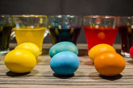 Transparent glass cups with water mixed with dry color. The process of coloring easter eggs concept. Happy Easter background. Stok Fotoğraf