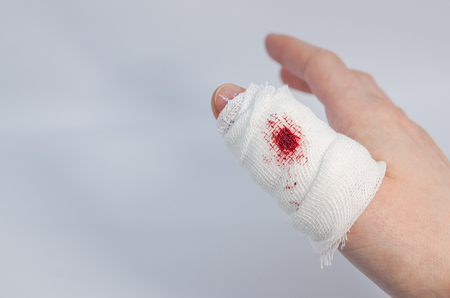 a piereced finger in bloody bandage . An accident consequences concept. An injured part of body.