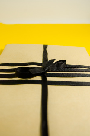 A handmade gift in brown wrapping paper and with a black ribbon.  A present for birthday on a yellow background close up view. Texture background of a holiday preparations.