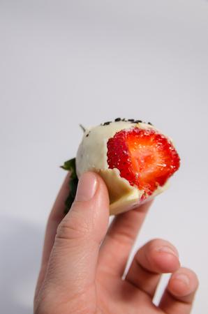 Erdbeere in dunkler Schokolade ist bereits gegessen. Geschmolzene Schokolade getauchte Erdbeeren für Schokoriegel. Hintergrund der frischen Wüsten.