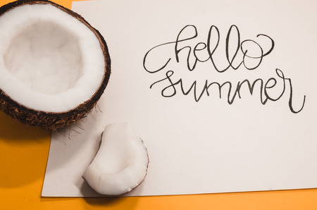 Summer is coming concept.  A white paper where is wtitten with nice handwriting - Hello Summer. Summer vibes with a half of ripe coconut on the orange background