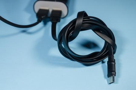 Bloc de charge noir avec deux cordons pour téléphone portable sur fond bleu. Gardez la batterie chargée sur votre appareil de toute façon. La technologie se connecte avec une prise électrique USB en gros plan.