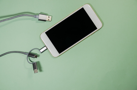 Usb cable with three different point ends charging a mobile phone. Technology connect close up. Charge diffrent types of devices with one cord.