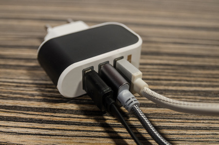 White charging block with three phone cables on wooden table background. Keep the battery charged on your devices concept. Technology connect with USB electrical plug close up.