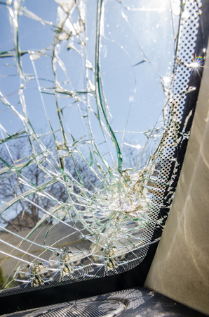 a broken glass background. Frontal window of the car is shattered. Stock Photo