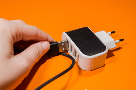 A hand pluging cable into phone adapter block on orange background. Keep the battery charged on your device anyway you go. Tehnology connect close up.