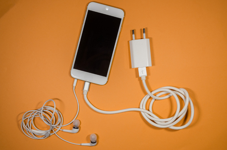 a phone with white usb cable block and headphones on orange background. Keep the battery charged and listen to music on your device anyway you go. Tehnology connect close up.