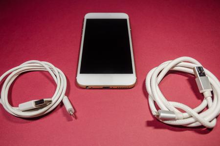 un téléphone avec deux câbles USB sur fond rouge. Gardez la batterie chargée sur votre appareil de toute façon. La technologie se connecte de près. Banque d'images