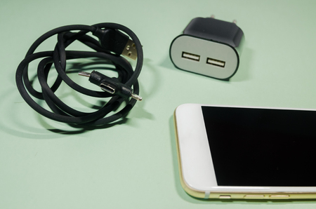 a mobile phone in the middle of black usb cable with different point ends and block adapter on green background. Keep the battery charged on your device anyway you go. Tehnology connect close up.